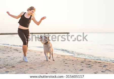 young caucasian female playing with siberian husky dog on beach during sunrise - stock photo