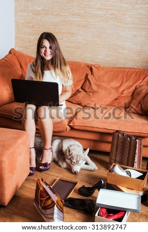 young caucasian female with laptop and shopping bags in living room. Woman tired of shopping. Female and little husky dog after shopping at home - stock photo