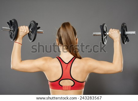 Young caucasian fitness woman working with dumbbells, studio shot - stock photo
