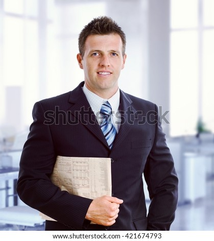 Young caucasian formal broker with newspaper under arm at business office. Smiling, standing, looking at camera, suit and tie. - stock photo