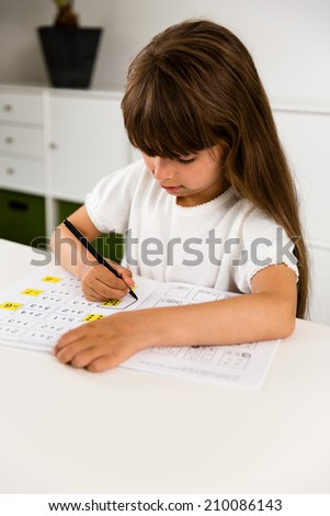 Young caucasian girl doing her homework while sitting at table. - stock photo