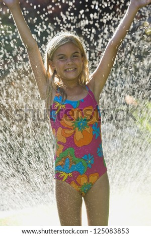 Young caucasian girl in sprinkler - stock photo