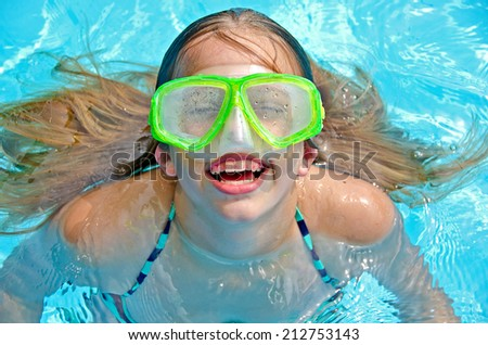 young Caucasian girl  smiling with dental braces and swimming goggles in pool - stock photo