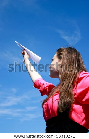 Young caucasian girl with paper plane in the hand - stock photo