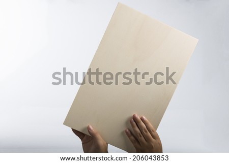 Young caucasian hands holding a light color plywood square blank signboard isolated on white background. There are no elements to distract viewer from reading any  message written on the oblique sign - stock photo