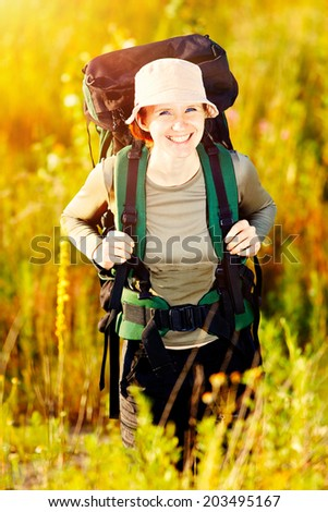Young caucasian hiking woman with backpack happily smiling - stock photo