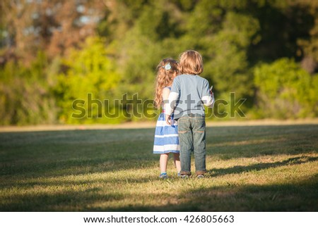Young Caucasian kids looking on the field during the sunset on a summer day. Also available in vertical format. - stock photo