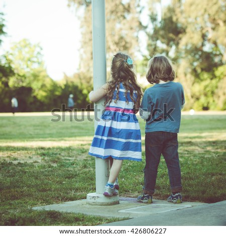 Young Caucasian kids looking on the field during the sunset on a summer day. Instagram view. Also available in horizontal format. - stock photo