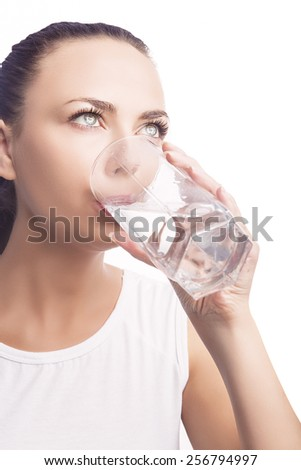 Young Caucasian Lady Drinking Water from Glass. Standing Isolated Over White Background. Vertical Image Composition - stock photo