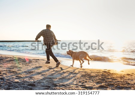 young caucasian male playing with labrador on beach during sunrise or sunset. Man and dog having fun on seaside - stock photo