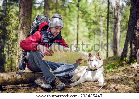 young caucasian male with a map and siberian husky dog in the forest, hiker looking at map outdoors - stock photo