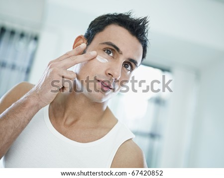 young caucasian man applying eye cream on face. Horizontal shape, front view, head and shoulders - stock photo