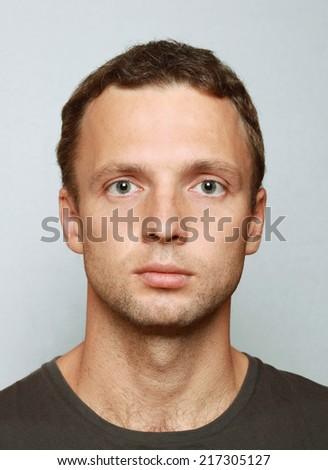 Young Caucasian man closeup portrait. Headshot on gray - stock photo