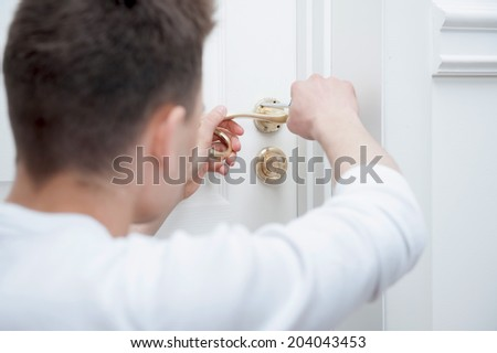 Young Caucasian man fixing the door handle with screwdriver from behind - stock photo
