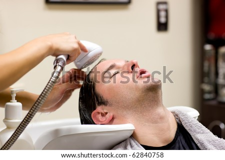 Young caucasian man having his hair washed in a hairdressing salon - stock photo