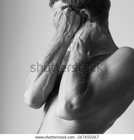 Young Caucasian man hides behind his strong blocking hands, black and white studio photo - stock photo