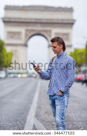 Young caucasian man holding a phone on the Champs Elysees in Paris - stock photo