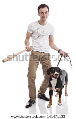 Young Caucasian man holding bat, with Entlebucher Sennenhund dog over white - stock photo