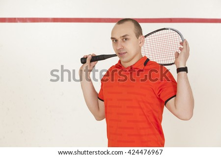 Young Caucasian man in a red t-shirt with racket squash. It should be on the court, looking at the camera and smiling. - stock photo