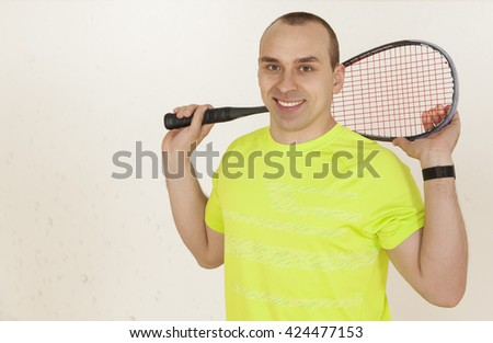 Young Caucasian man in a yellow T-shirt with racket squash. It should be on the court, looking at the camera and smiling. Horizontal color image. - stock photo