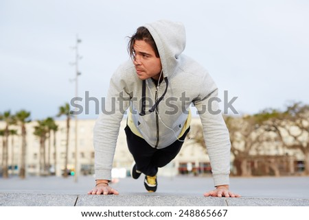 Young caucasian man in sweatshirt doing push ups outdoors, fitness and sport lifestyle concept - stock photo