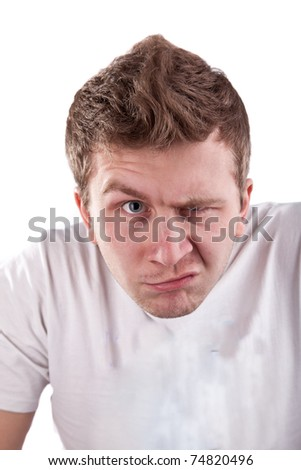 Young caucasian man is looking suspiciously with one eye - stock photo