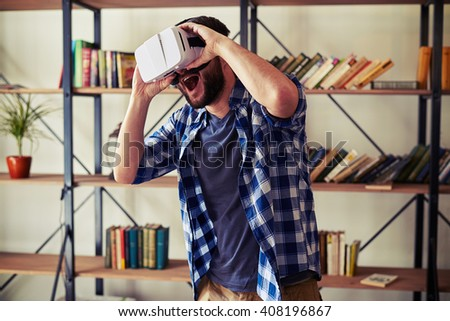 Young Caucasian man playing computer game in white virtual reality headset glasses - stock photo