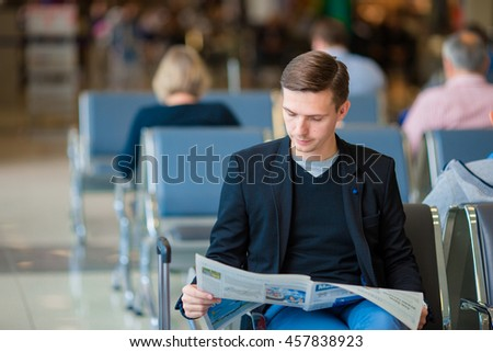 Young caucasian man with newspaper at the airport while waiting for boarding. Casual young businessman wearing suit jacket. - stock photo
