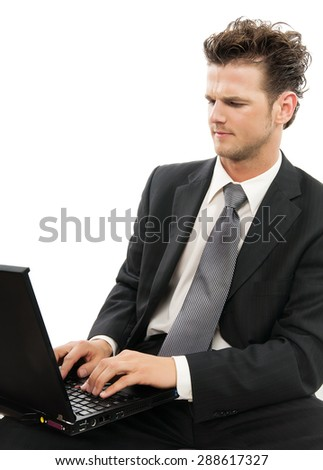 Young Caucasian man working on laptop indoors over white background. Concerned skeptical looking businessman. - stock photo