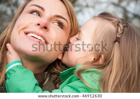 Young caucasian mother listens her toddler daughter whispering with smile - stock photo