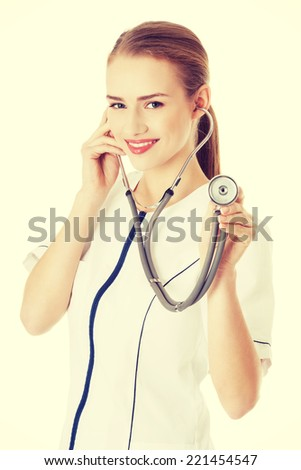 Young caucasian nurse or doctor is listening through stethoscope. Isolated on white. - stock photo