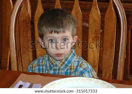 Young caucasian preschool age boy sitting at a wood dining room table waiting for food. Not sure he wants what is being served. concerned expression. - stock photo