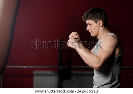 Young caucasian sportsman hit a punch bag, boxing, warming up in fitness center - stock photo