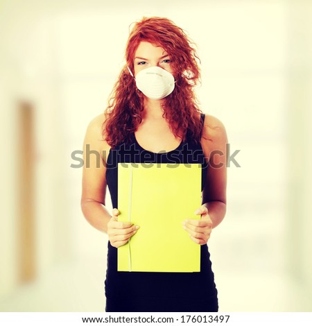 Young caucasian student woman with mask on her face. She is defending her self from viruses. - stock photo