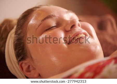 Young caucasian teenage girl smiling with her eyes closed as she relaxes during her  luxurious facial - stock photo