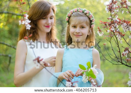 Young caucasian woman and her little daughter in spring garden - stock photo