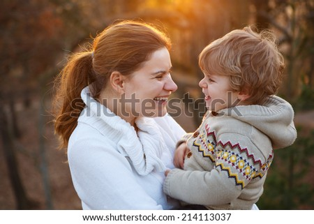 Young caucasian woman and little son hugging in evening light, outdoors - stock photo