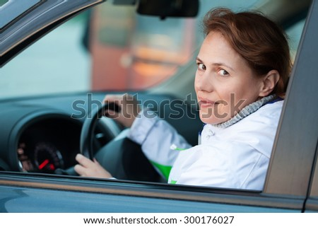 Young Caucasian woman as a driver in a car, outdoor closeup portrait - stock photo