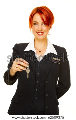 young caucasian woman as hotel worker offering key - stock photo
