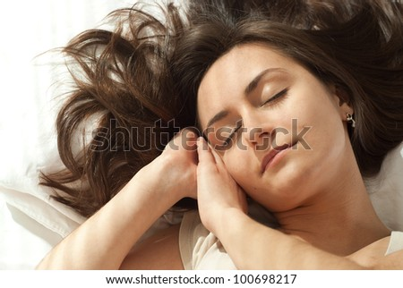 Young Caucasian woman asleep in bed on a light background - stock photo
