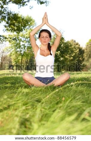 Young caucasian woman doing yoga exercise outside in the park - stock photo