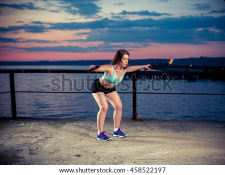 Young caucasian woman exercising with dumbbells on sea pier. Fitness workout outdoors - stock photo