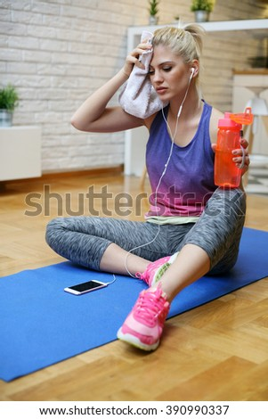 Young Caucasian woman filing tired, drinking water during workout at home. - stock photo