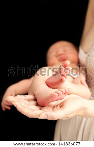 Young caucasian woman holding newborn son, shallow depth of field - stock photo