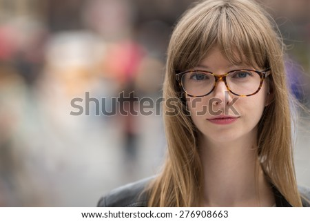 Young caucasian woman in city serious face portrait - stock photo
