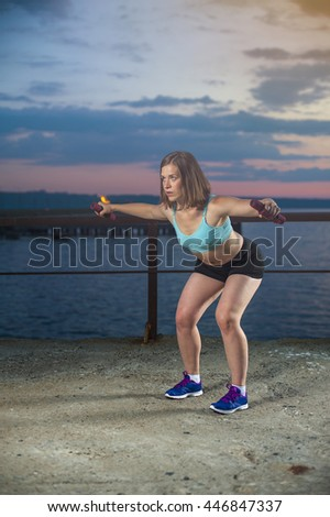 Young caucasian woman in sportswear doing exercises with dumbbells. Fitness workout outdoors. - stock photo