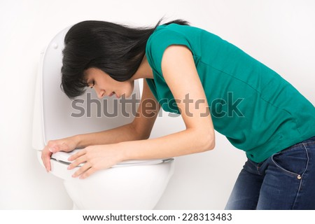 Young caucasian woman in toilet - pregnant, drunk or illness concept. Young dark-haired woman vomiting in toilet - stock photo