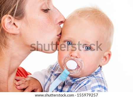 Young Caucasian woman kissing her baby son over white, closeup view - stock photo