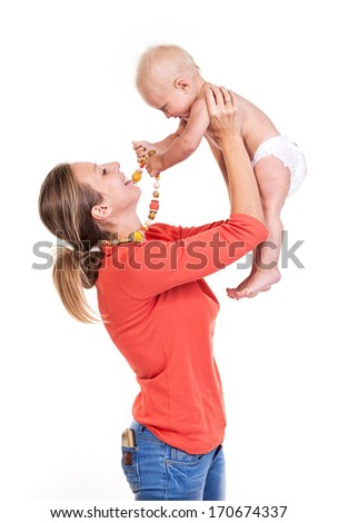 Young Caucasian woman lifting her baby son over white, boy playing with nursing necklace - stock photo