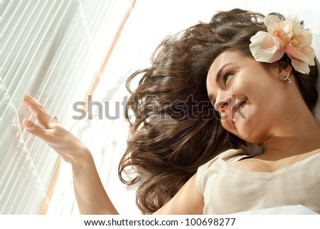 Young Caucasian woman lying in bed with flowers on a light background - stock photo